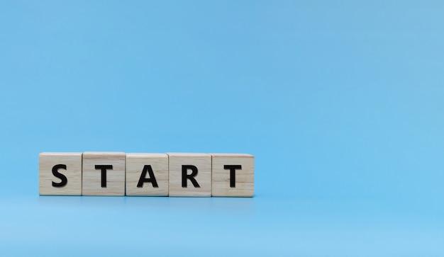 Commencez. mot start écrit sur une pile de blocs de cubes en bois sur fond bleu, félicitations pour le nouvel an, tendance, idée, finance, stratégie, démarrage d'entreprise, marketing en ligne, concept d'objectif et de plan cible