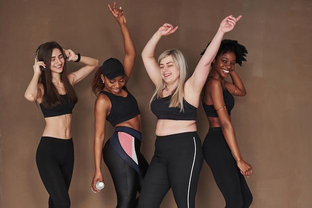 Commençons la fête. groupe de femmes multiethniques debout contre l'espace brun