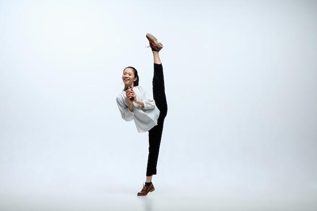 Commençons par le café aromatique. heureuse femme travaillant au bureau, sauter et danser dans des vêtements décontractés ou costume isolé sur fond de studio blanc. entreprise, start-up, concept d'espace ouvert de travail.