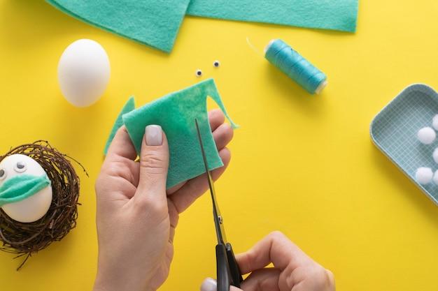 Comment faire un lapin en feutre pour la décoration et le plaisir de pâques. concept de bricolage. instruction étape par étape. étape 11. découpez les oreilles de lapin dans du feutre.