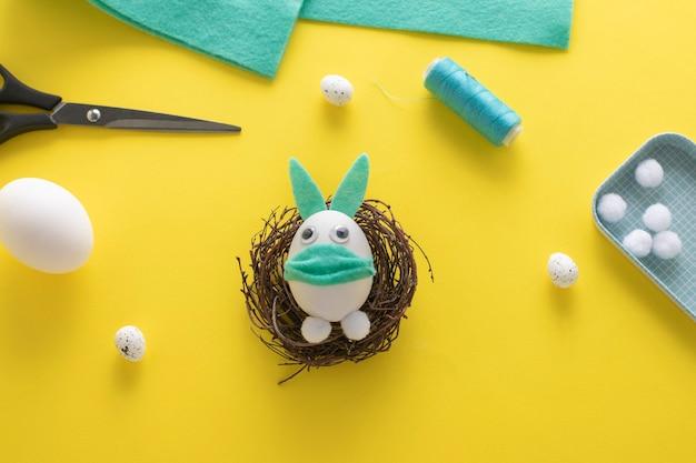 Comment faire un lapin en feutre pour la décoration et le plaisir de pâques. concept de bricolage. instruction étape par étape. étape 15. un lapin drôle d'un œuf dans un masque est prêt!