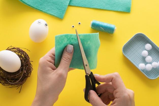 Comment faire un lapin d'oeuf pour la décoration et le plaisir de pâques. concept de bricolage. instruction étape par étape. étape 3. découpez un rectangle de feutre.