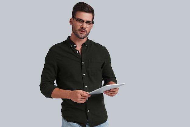 Comment puis-je vous aider? beau jeune homme à lunettes tenant sa tablette numérique et regardant la caméra en se tenant debout sur fond gris