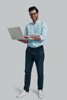 Comment puis-je vous aider? toute la longueur du jeune homme utilisant un ordinateur portable et regardant la caméra avec le sourire en se tenant debout sur fond gris