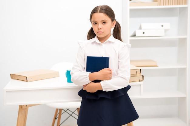 Comment rendre l'éducation plus intéressante pour les premiers élèves une petite fille tient un livre en se tenant debout