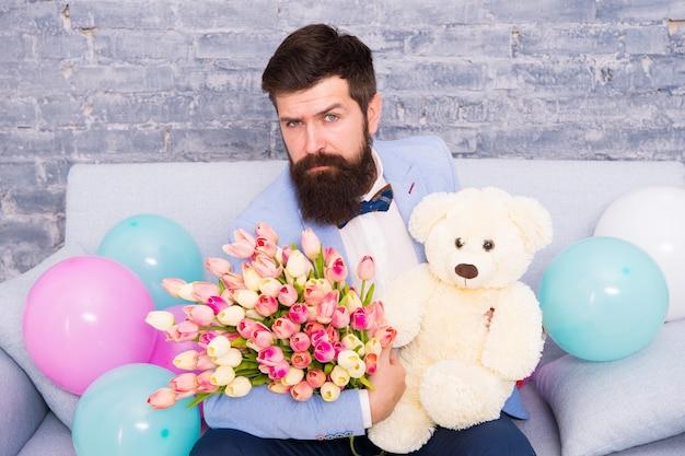 Comment réussir à lui demander de sortir avec. un homme romantique avec des fleurs et un ours en peluche s'assoit sur le canapé en attendant sa petite amie. cadeau romantique. rendez-vous romantique prêt macho. l'homme porte un nœud papillon de smoking bleu tenir un bouquet de fleurs.