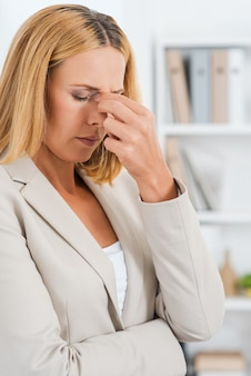 Comment vais-je passer cette journée ? femme d'affaires mûre déprimée touchant son nez