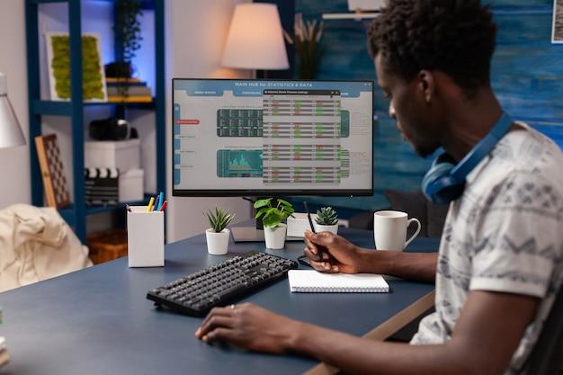 Commerçant afro-américain écrivant des données de crypto-monnaie sur un ordinateur portable
