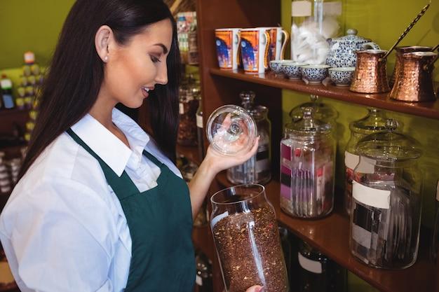Commerçant femme tenant un pot d'épices