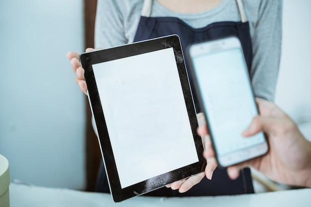 Le commerçant en gros plan sert le paiement en ligne du code-barres qris du client