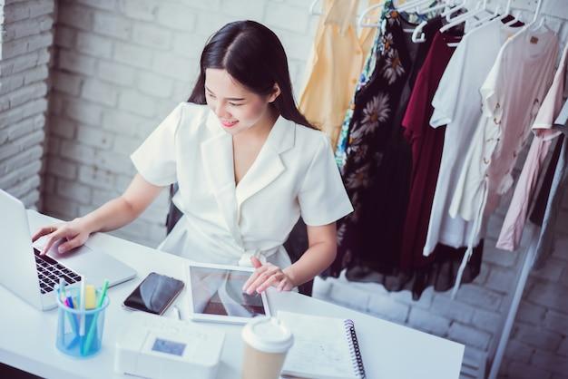 Les commerçants en ligne vendant des vêtements à l'aide d'une calculatrice à partir d'une tablette calculent les coûts.