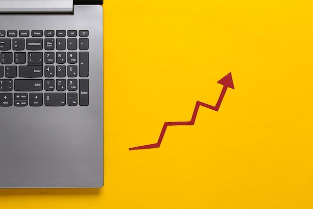 Commerce en ligne, commerce. ordinateur portable et flèche de croissance rouge sur jaune. graphique de flèche qui monte.