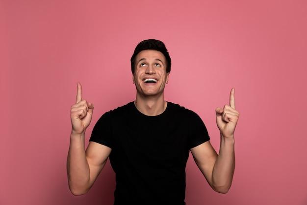 Commercial. bel homme dans un t-shirt noir, qui regarde et pointe vers le haut en souriant.