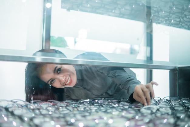 Une commis de magasin jette un coup d'œil dans la fenêtre en verre pour ramasser les verres du choix d'un client chez un opticien
