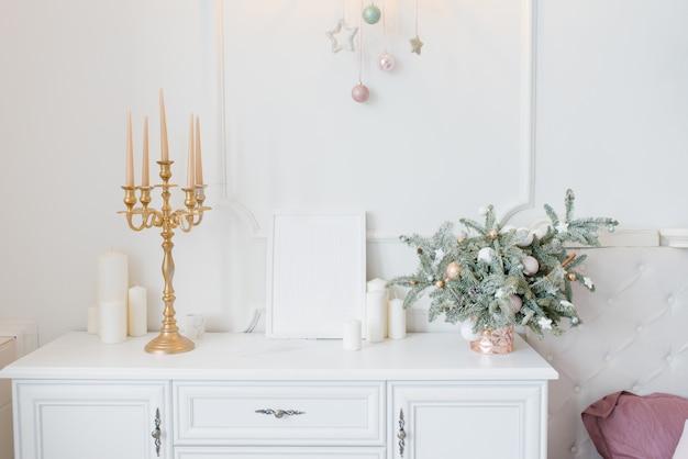 Commode blanche dans la chambre ou le salon, chandelier, arrangement en épicéa et bougies