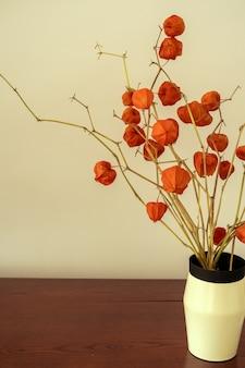 Commode en bois avec des branches florales dans un vase