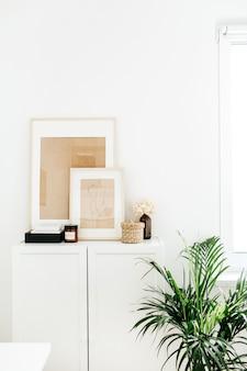 Commode, cadres photo, plante de palmier et décor