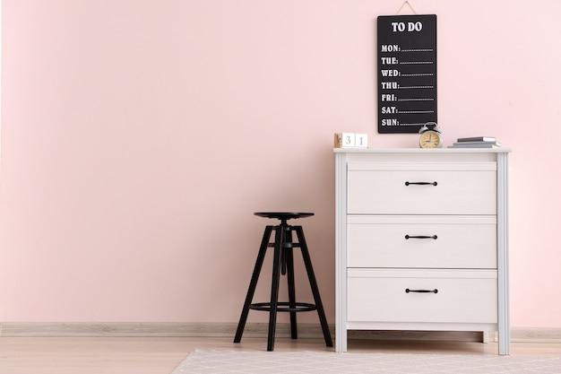 Commode moderne avec tabouret près du mur de couleur au bureau