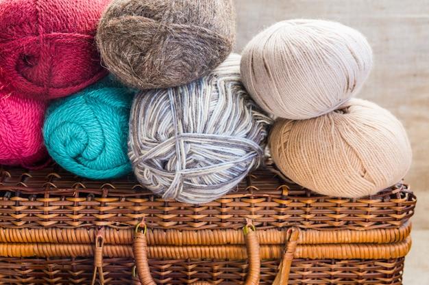 Commode en osier vintage, pinces, boules de fil de laine multicolore