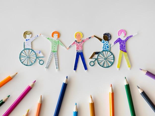 Communauté de personnes multiethniques et handicapées avec des crayons