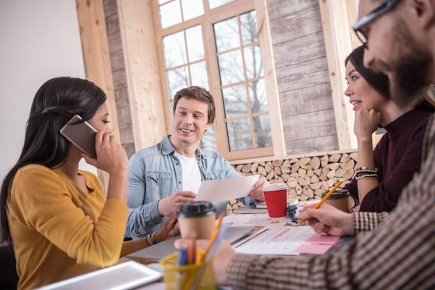 Communication à distance. ravie belle femme positive assise à la table et passer un appel tout en travaillant avec ses collègues
