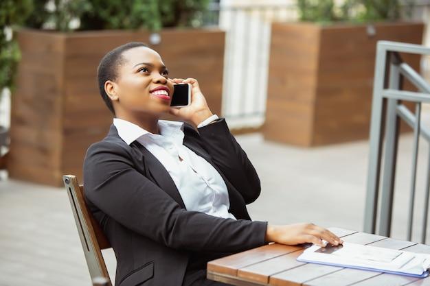 La communication. femme d'affaires afro-américaine en tenue de bureau souriante, a l'air confiante et heureuse, occupée. concept de finance, d'entreprise, d'égalité et de droits de l'homme. belle jeune femme modèle, réussie.
