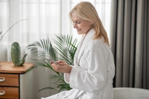 La communication. une femme dans un peignoir blanc textos sur un smartphone