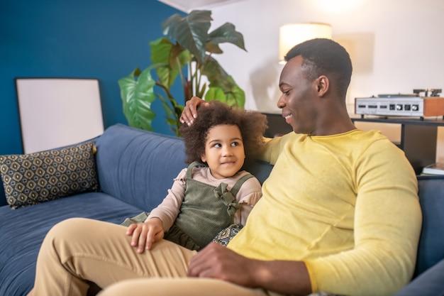 La communication. jeune papa à la peau foncée touchant la tête de sa petite fille communiquant assis sur un canapé dans une chambre confortable