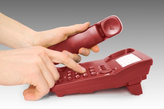 La communication. téléphone de bureau rouge avec numérotation mains