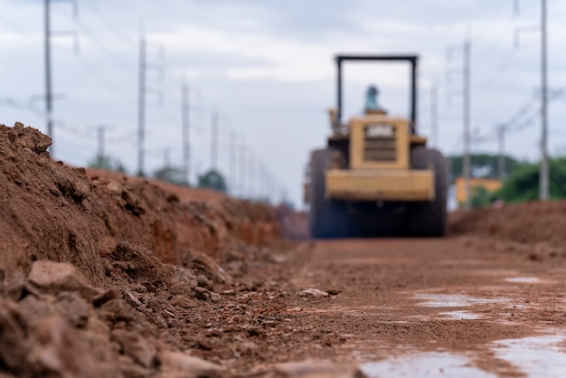Compacteur de sol vibrant jaune flou travaillant sur la construction de routes