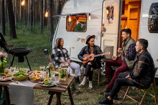 Compagnie amicale assise près d'une maison sur roues et chantant des chansons