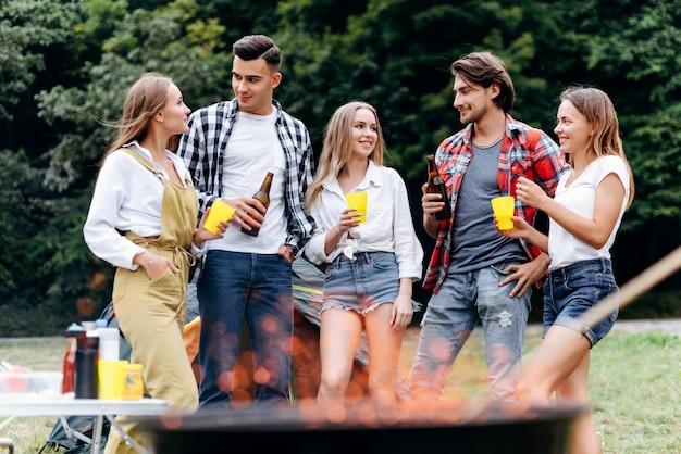 Une compagnie d'amis au camp soulève une bouteille de bière et s'amuse au camping