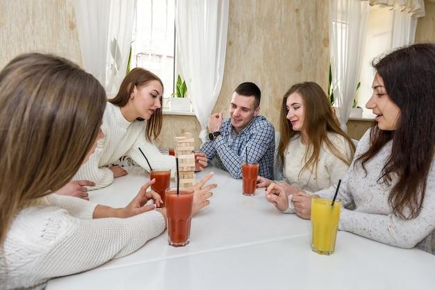 La compagnie d'amis boit du jus et joue au jeu de la tour dans le café