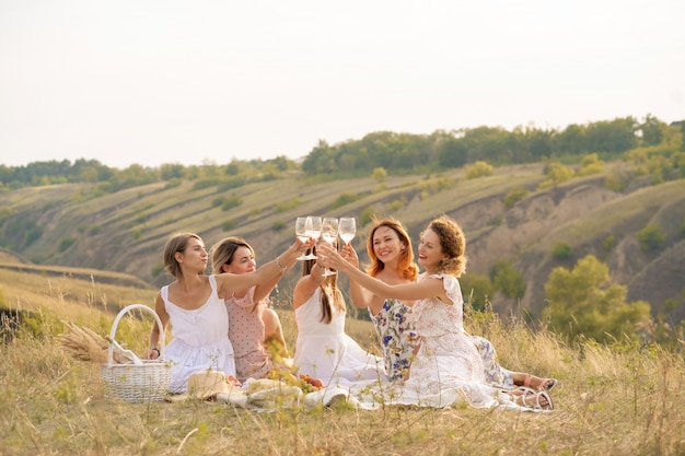 La compagnie d'amis féminines profite d'un pique-nique d'été et soulève des verres de vin