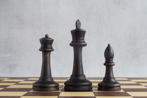Une compagnie d'échecs noirs sur l'échiquier un roi une reine et un fou