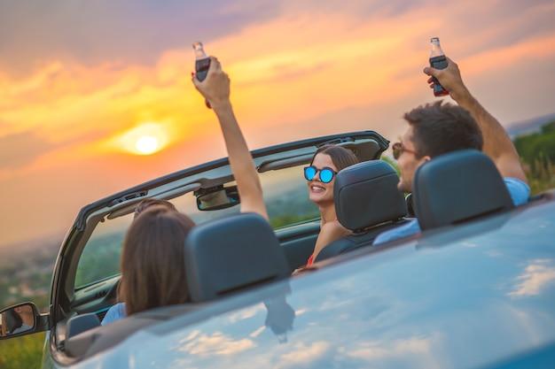 La compagnie des gens s'assoit dans un cabriolet sur fond de coucher de soleil