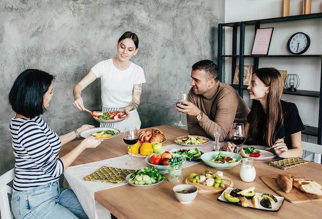 Compagnie d'hommes et de femmes à la maison à une table avec des boissons et de la nourriture s'amusant et bavardant