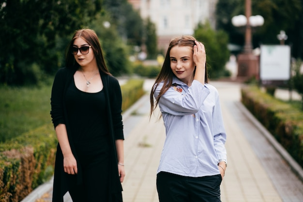 Compagnie de jeunes amis avec smartphones marchant dans la ville