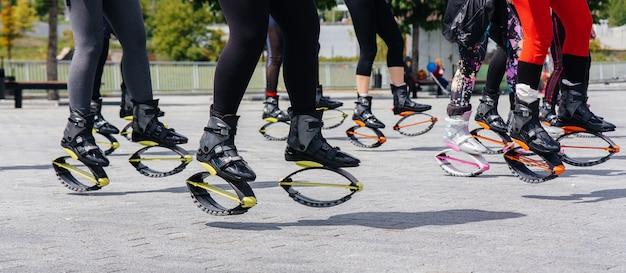 La compagnie de jeunes filles attrayantes est engagée dans l'aérobic en plein air. mode de vie sain. gros plan de chaussures de sport.