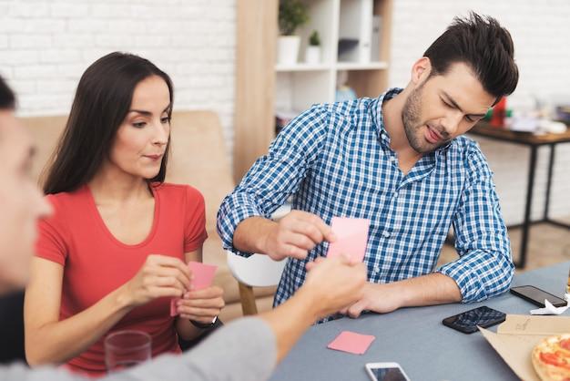 La compagnie des jeunes joue aux cartes.