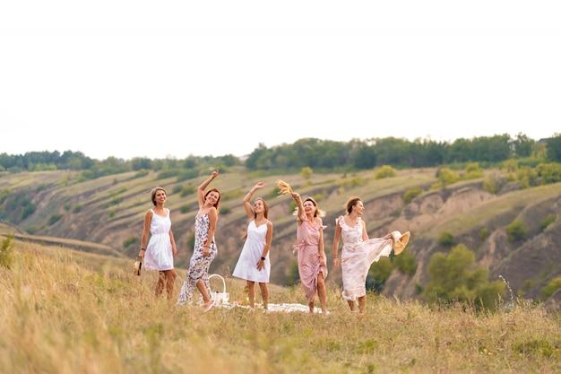 La compagnie de joyeuses amies passe un bon moment ensemble lors d'un pique-nique dans un endroit pittoresque surplombant les collines verdoyantes