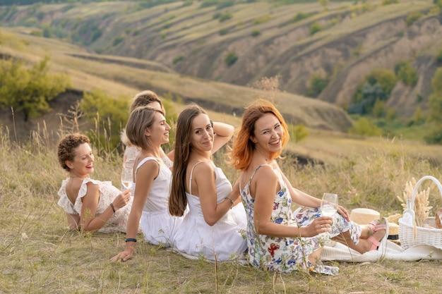 La compagnie de joyeuses amies en robes blanches bénéficie d'une vue sur les collines verdoyantes, se détendant lors d'un pique-nique.