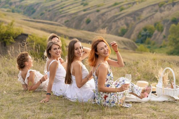 La compagnie de joyeuses amies en robes blanches jouit d'une vue sur les collines verdoyantes, se détendant sur un pique-nique.