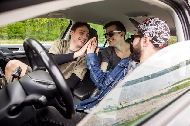 Compagnie de joyeux amis se saluant en voiture