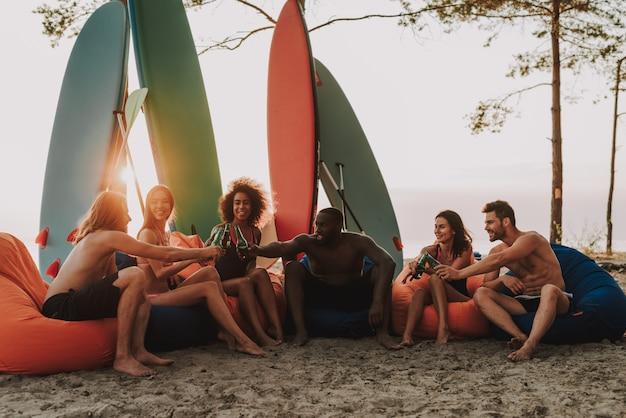 Compagnie portant sur les ottomans. fête sur la plage.