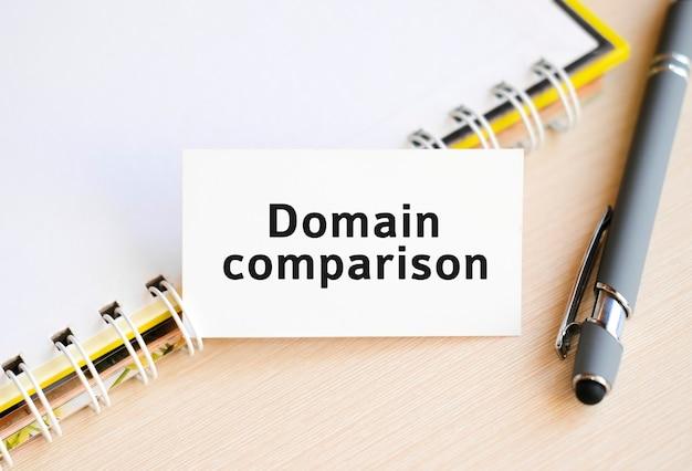 Comparaison de domaine - texte sur un ordinateur portable avec un ressort et un stylo gris