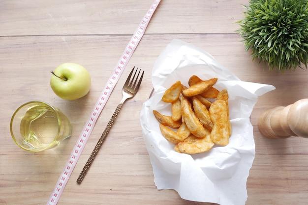 Comparaison des quartiers de pommes et de pommes de terre mangeant un concept de nourriture saine