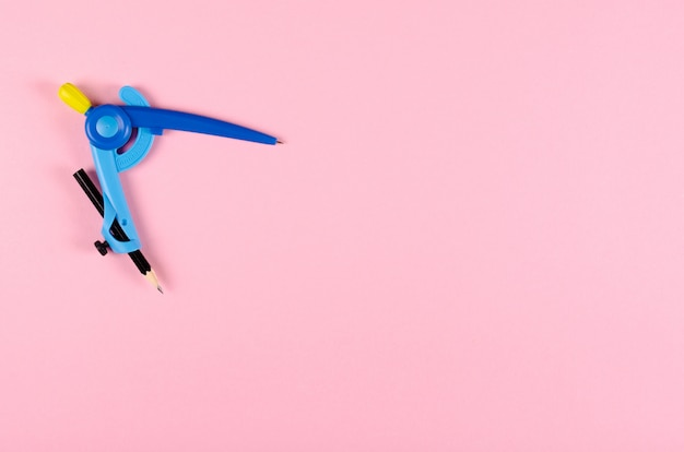 Compas bleu de papeterie pour les enfants sur fond rose.