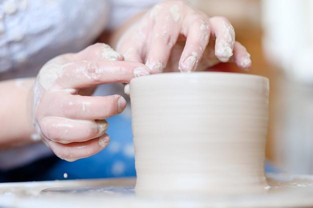 Compétences artisanales de poterie. art traditionnel de la création de la céramique. pâte à modeler potter sur la roue tournante