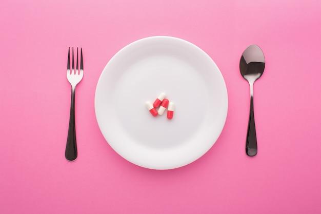 Complément alimentaire sur plaque avec fourchette et cuillère sur rose, vue du dessus